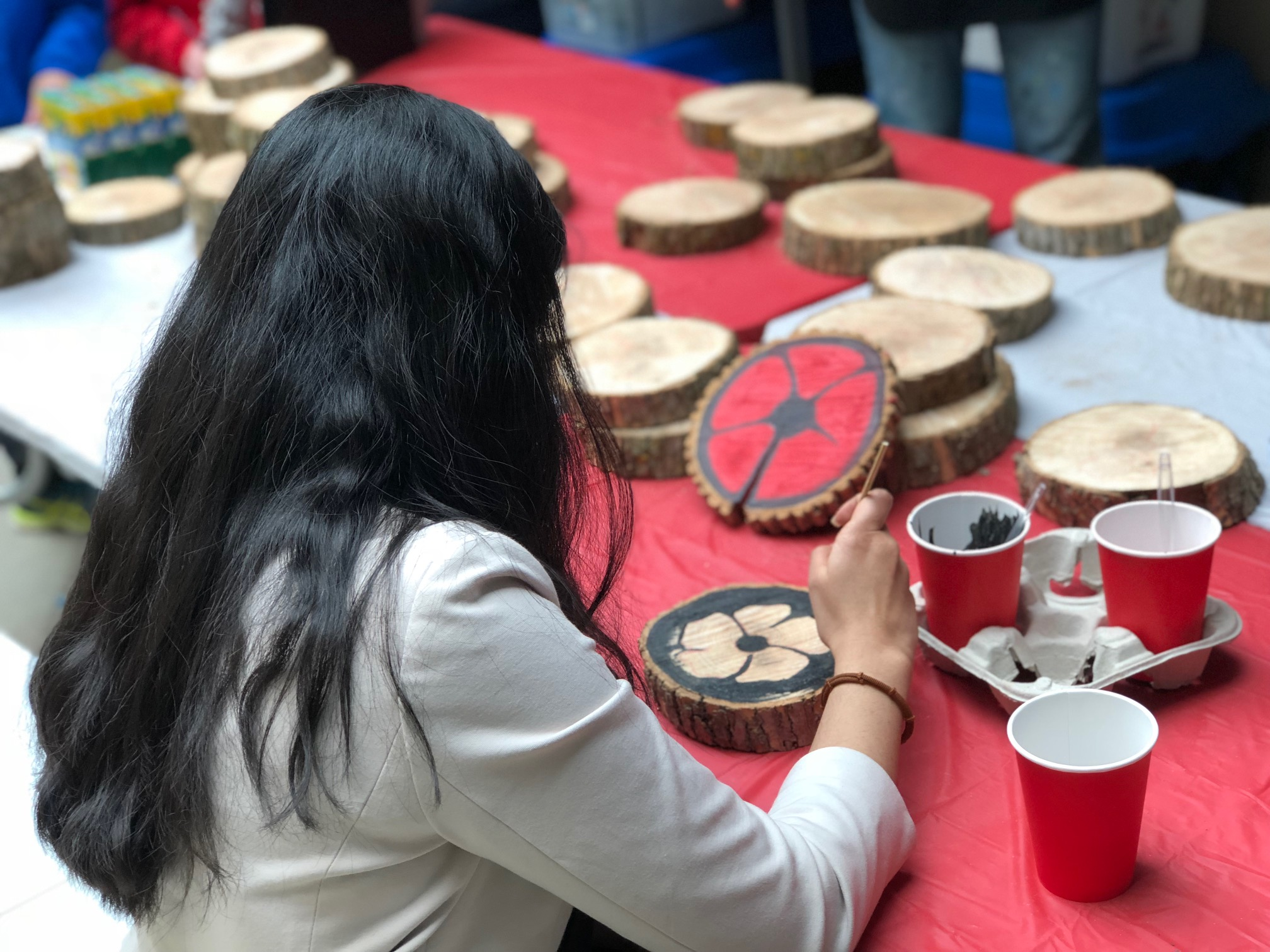 girl painting wooden poppy